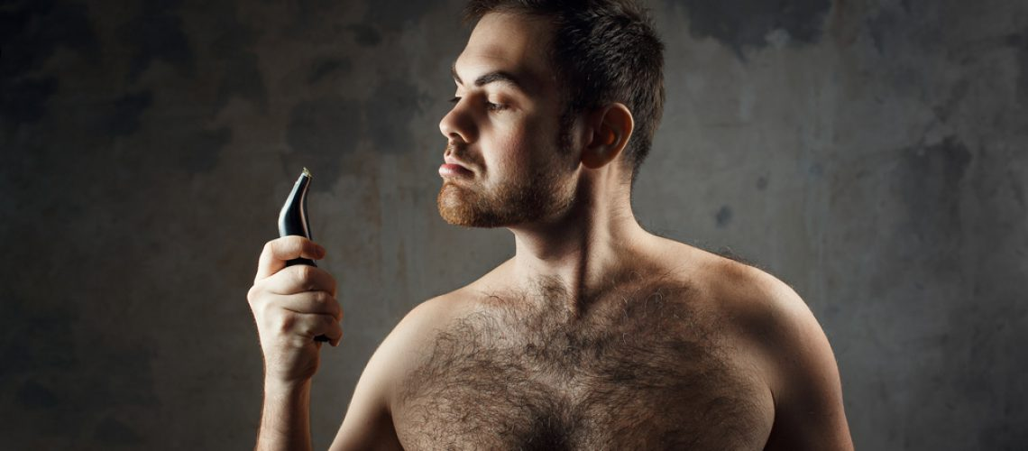 Hairy man with a naked torso holding an electric razor before shaving.