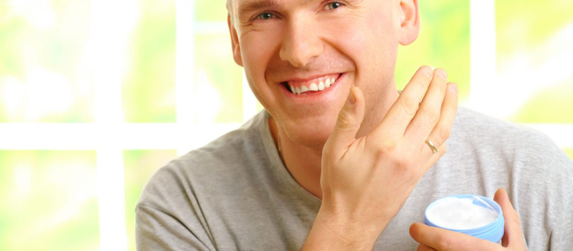 Happy man wearing casual clothes applying facial cream on skin.