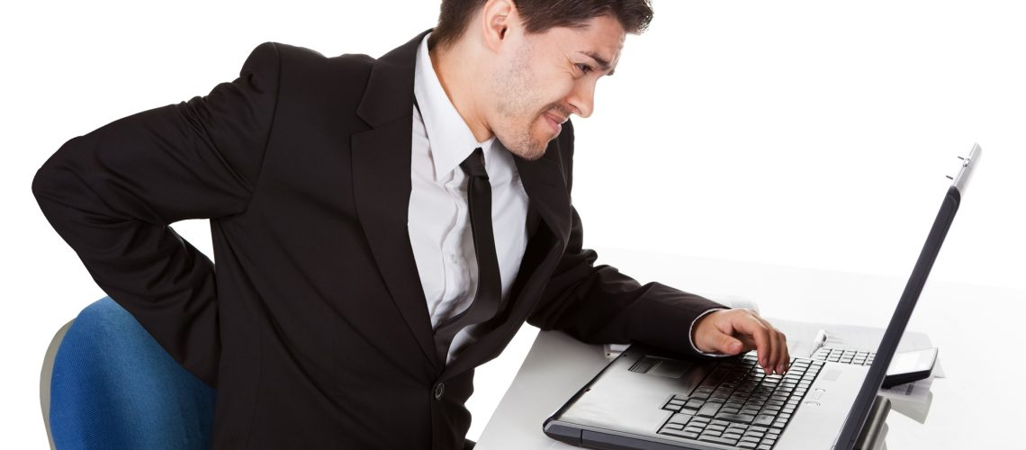 Businessman with lower back ache from sitting with a bad posture in his office chair working on his laptop massaging his back with his hand