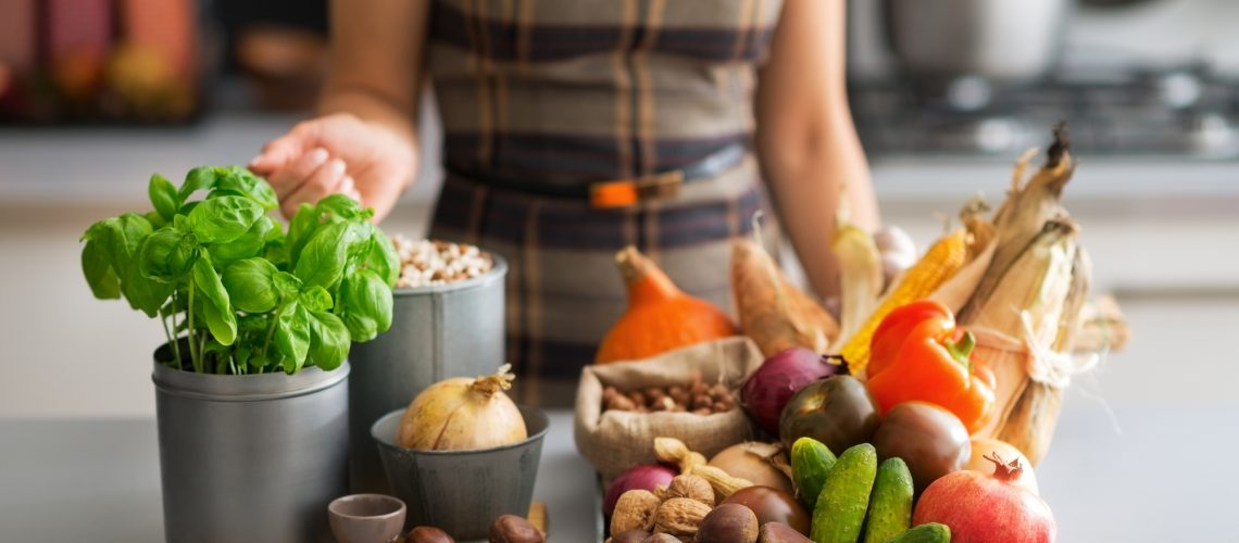 Closeup on young housewife with vegetables in kitchen