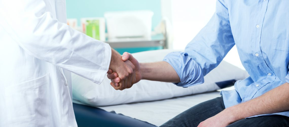 Doctor and patient handshake with medical equipment on the background.