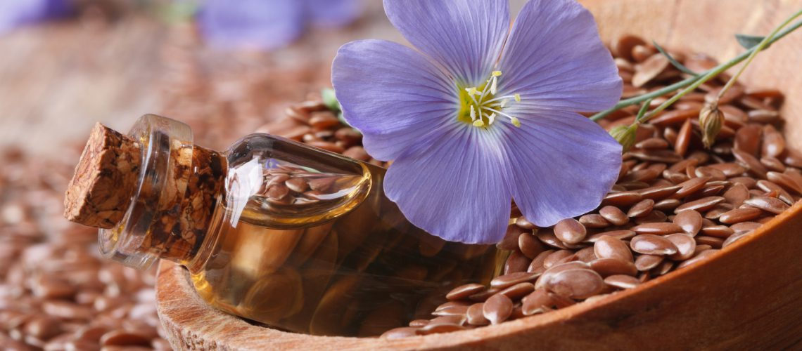 flax oil in a glass bottle, flowers and seeds in a wooden spoon macro horizontal