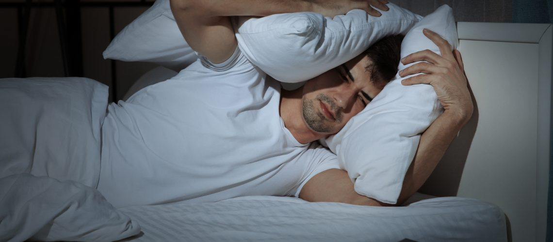 Handsome young man suffering from headache while lying in bed at night