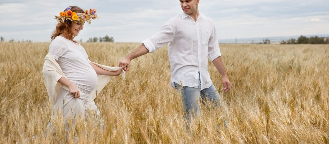 Outdoor portrait of young pregnant couple in field