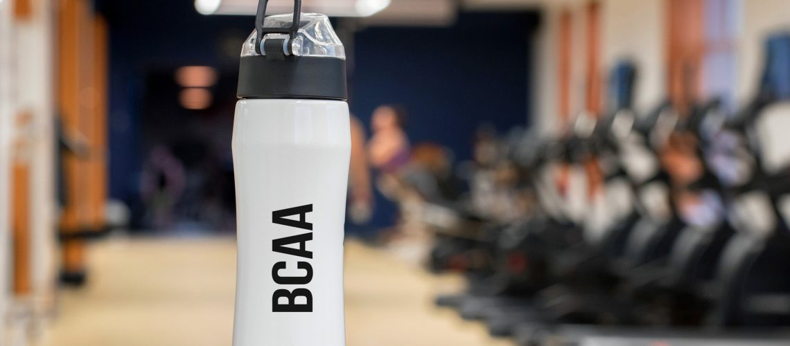 White fitness bottle with branched-chain amino acid and blurred background with people exercising in gym
