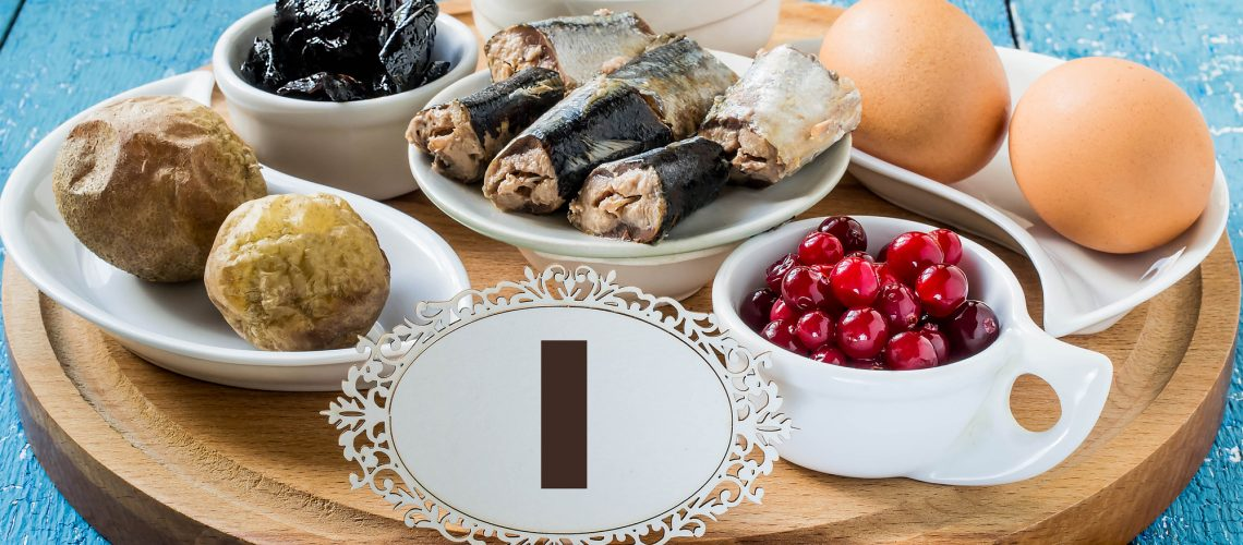 Products containing iodine (seaweed, boiled eggs, cranberries, sardines, baked potatoes, prunes) on a round cutting board and a blue wooden background
