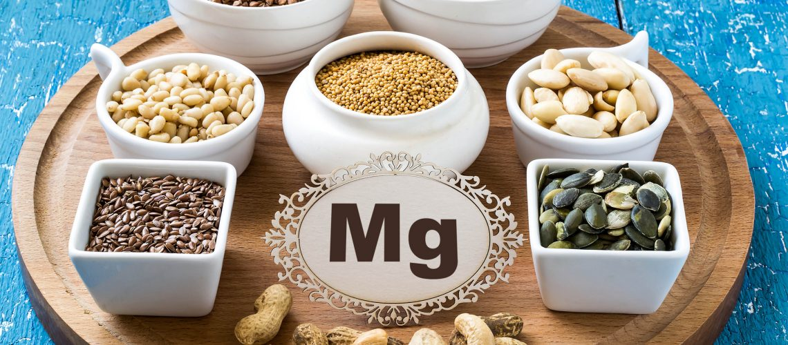 Collection products containing magnesium (buckwheat, cashews, peanuts, pine nuts, almonds, flax seeds and pumpkin, mustard, seaweed) on a round cutting board and a blue wooden background