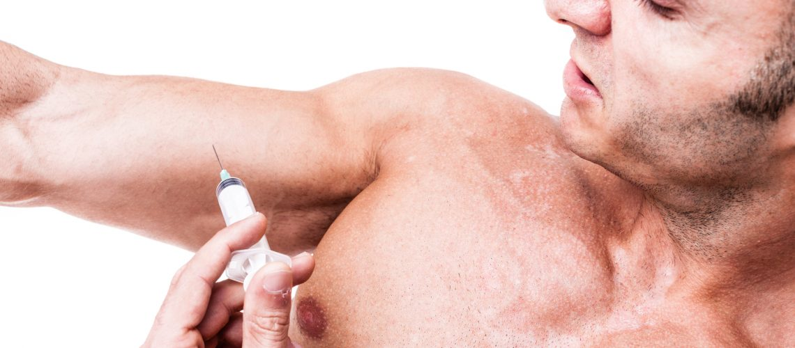 a muscular man giving himself a steroid injection in his arm